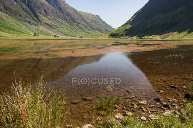 United Kingdom, Scotland, Highland, Ballachulish, Lake in Glencoe Highland scenic landscape with green meadow and mountains — Stock Photo
