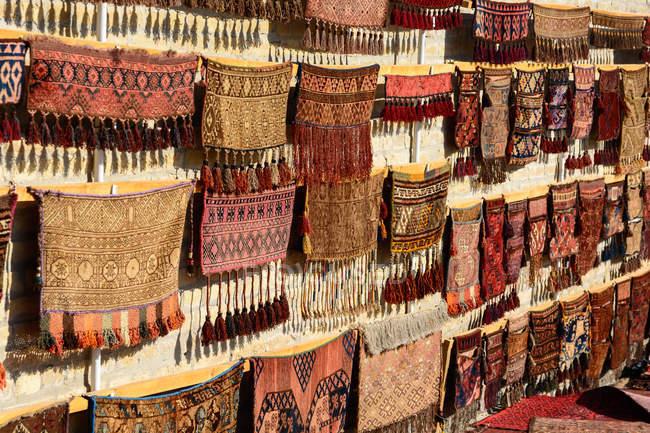 Узбекистан, провінція Бухара, Бухара, перськими килимами, висить на полиці — стокове фото