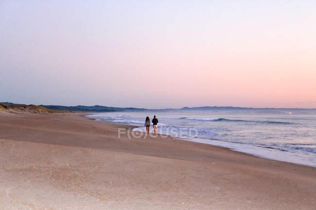 Nouvelle-Zélande, Île du Nord, Northland, Waipu, Sunrise et couple marchant sur la plage — Photo de stock