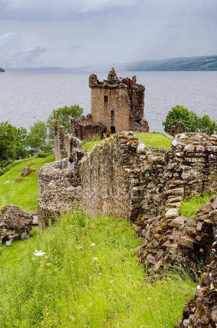 United Kingdom, Scotland, Highland, Inverness, Moray Firth, View of the Castle Ruins Urquhart Castle on green hills by lake — Stock Photo