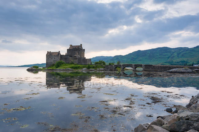 Reino Unido, Escócia, Highland, Dornie, Loch Duich, Eilean Donan Castle, Scottish Clan Clan Macrae, Eilean Donan Castle em paisagem cênica com lago refletindo céu — Fotografia de Stock
