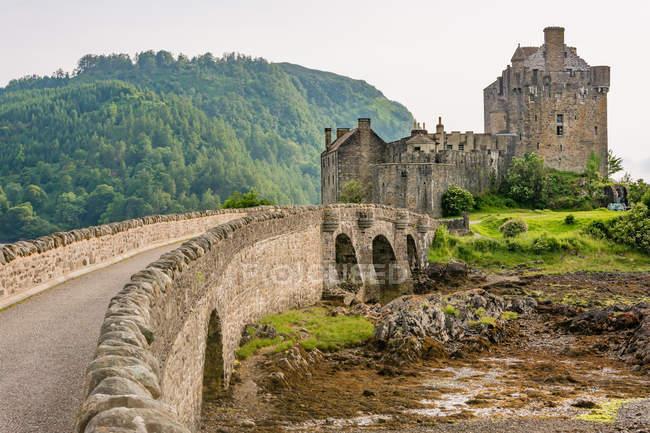 United Kingdom, Scotland, Highland, Dornie, Loch Duich, Eilean Donan Castle with bridge in green landscape — Stock Photo