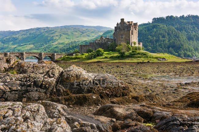 United Kingdom, Scotland, Highland, Dornie, Loch Duich, Eilean Donan Castle with bridge in natural landscape — Stock Photo