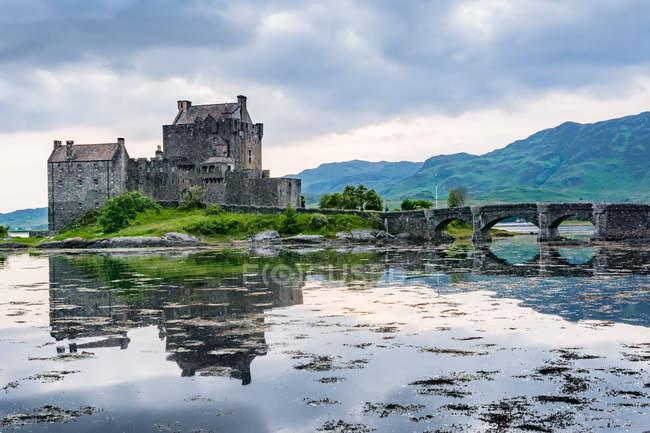 Reino Unido, Escócia, Highland, Dornie, Loch Duich, Eilean Donan Castle com ponte sobre lago com reflexão do céu — Fotografia de Stock