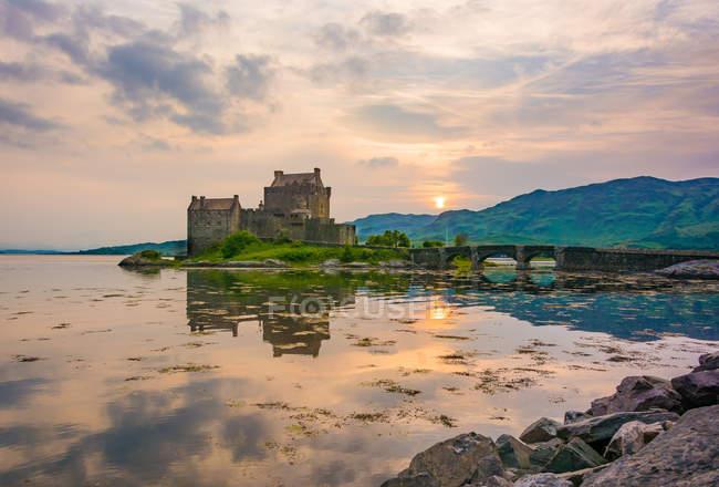 United Kingdom, Scotland, Highland, Dornie, Loch Duich, Eilean Donan Castle by lake at scenic sunset — Stock Photo