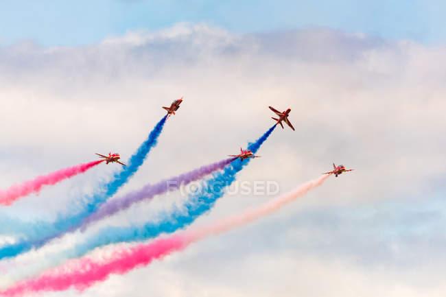 Reino Unido, Escocia, East Lothian, North Berwick, Flechas Rojas en el Scotlands National Airshow anual en East Fortune, la realización de aeronaves en el cielo dejando senderos coloridos, vista inferior - foto de stock