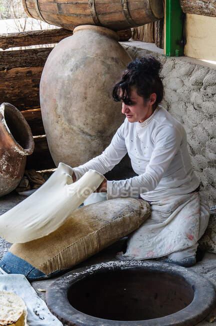 Армия, Котайк, Гарни, Лаваш - типичный армянский хлеб. Внутри дровяной каменной печи приклеивается тонкое тесто. Параллели с индийским Тандуром очевидны — стоковое фото