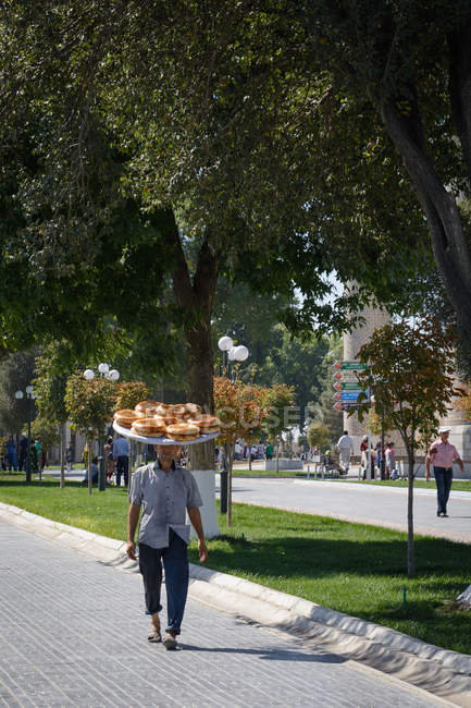 Person carrying on head plate with local bread on street of Samarkand, Samarkand Province, Uzbekistan — Stock Photo