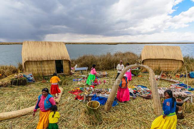 Einheimische Frauen arbeiten am grasbewachsenen Ufer der Insel Uros im Titicacasee, Puno, Peru — Stockfoto