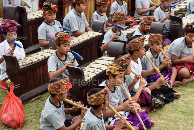 KABUL BULELENG, BALI, INDONESIA - 17 DE AGOSTO DE 2015: representación de la epopeya del Ramayana por la escuela de baile local, niños sentados en el suelo con ropa tradicional con instrumentos musicales - foto de stock