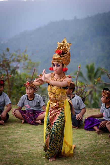 KABUL BULELENG, BALI, INDONESIA - 7 DE JUNIO DE 2018: Actuación al aire libre de la escuela de baile local, danza de niñas con disfraces, niños sentados en el fondo - foto de stock