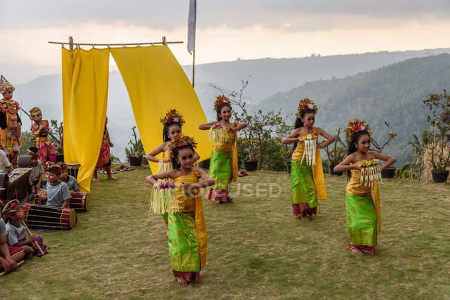 KABUL BULELENG, BALI, INDONESIA - 7 DE JUNIO DE 2018: Actuación al aire libre de la escuela de baile local, niñas bailando con disfraces, niños tocando música - foto de stock