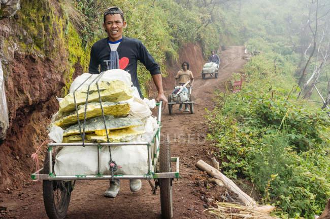 Java, Indonesien - 18. Juni 2018: Arbeiter Schwefel aus Vulkan Ijen in den Wagen zu transportieren — Stockfoto