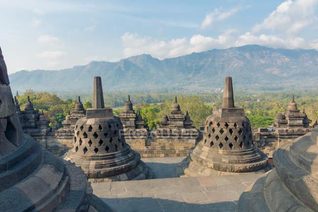 Indonésie, Java, Magelang, complexe de temple bouddhiste de Borobudur, Stupas et paysage de montagnes en arrière-plan — Photo de stock
