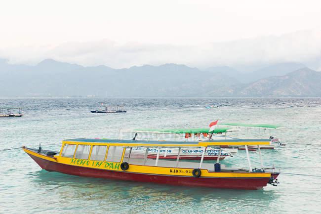 Indonésie, Nusa Tenggara Barat, Lombok Utara, sur l'île de Pulau Gili Meno, ferries et bateaux devant une chaîne de montagnes — Photo de stock