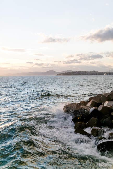 Греция, Аттика, Палео Фалиро, вечером на море, город на скалистом побережье на фоне — стоковое фото