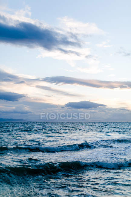 Greece, Attica, Paleo Faliro, view of the wide sea, breaking waves on the harbor wall in the evening light — Stock Photo