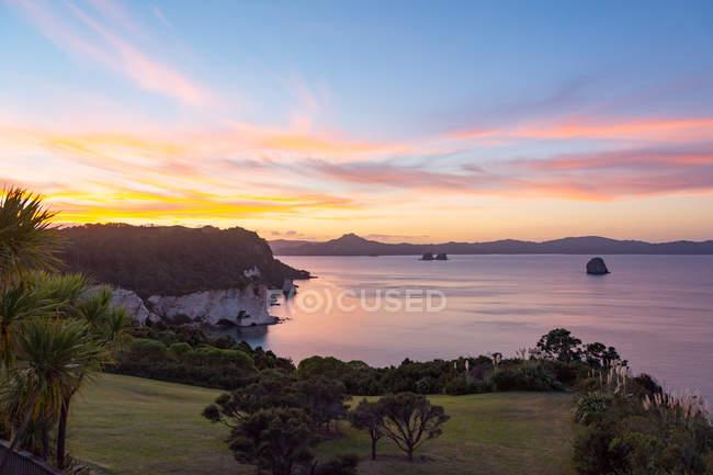 New Zealand, Waikato, Hahei, Scenic seascape with green coast at sunset — Stock Photo