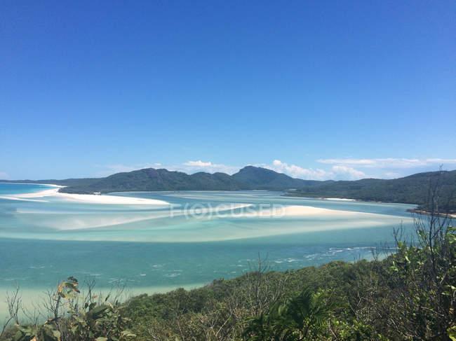 Australia, Queensland, Whitsundays, Whitsunday Islands, aerial seascape with grassy coast and mountains on background — Stock Photo
