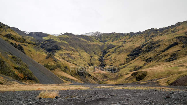 Bergige Landschaft mit entfernten Wasserfall, Island — Stockfoto
