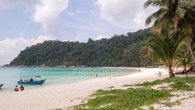 Malaysia, Terengganu, Kuala Besut, Forested Island with sandy beach - Perhentian Besar, people sitting on sand by boats — стокове фото
