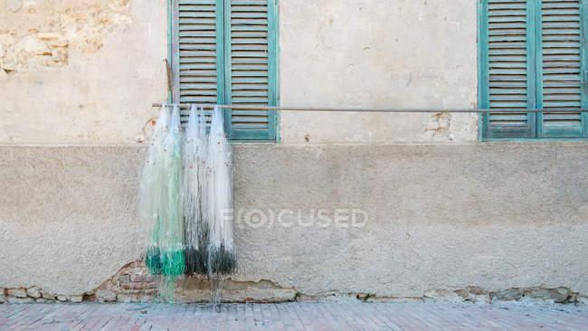 Italy, Umbria, Isola Maggiore, fishing net on pole on house wall, Lake Trasimeno — Stock Photo