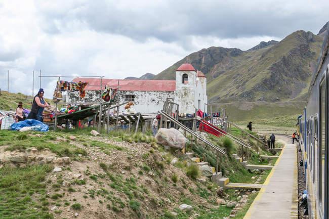 Les habitants de Qanchi pruwinsya, Qosqo (Pérou) font la lessive en train devant une église traditionnelle en traversant les Andes de Puno pour se rendre à Cusco.. — Photo de stock