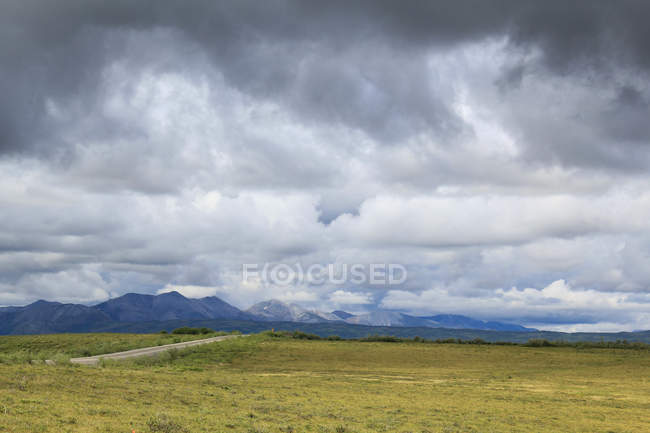 Canada, Yukon Territory, Yukon, On the Dampster Highway Judging North wilderness landscape with mountains under heavy sky — стоковое фото
