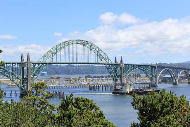 USA, Oregon, Rockaway Beach, view of ship sailing by a bridge — Stock Photo