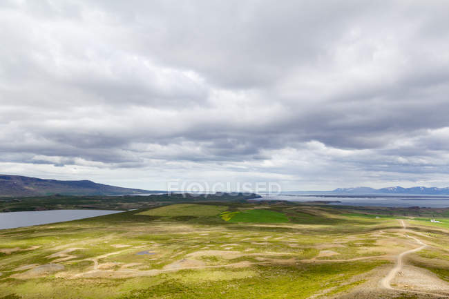Green fields and distant mountains under cloudy sky, Iceland — Stock Photo