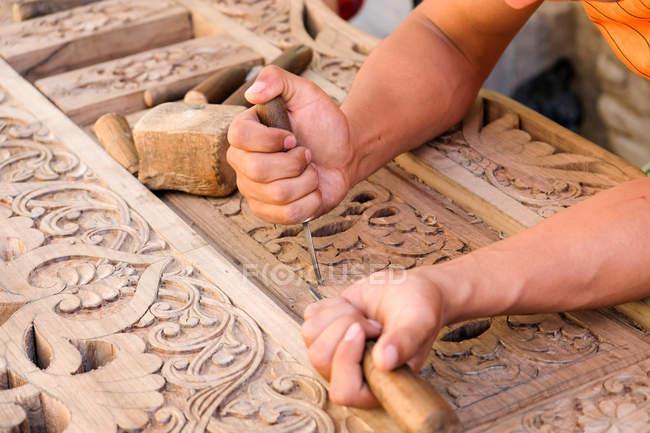 Узбекистан, мужские руки украшают традиционные деревянные двери — стоковое фото