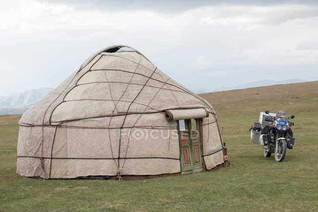 Kirguistán, región de Naryn, distrito de Kochkor, motocicleta estacionada junto a la yurta - foto de stock