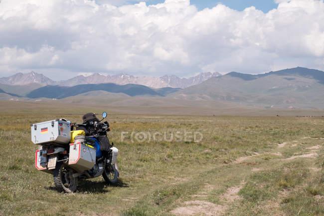 Kirghizistan, région de Naryn, district de Kochkor, moto garée dans domaine — Photo de stock