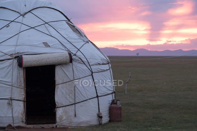 Kirguistán, región de Naryn, distrito de Kochkor, puesta de sol en el campamento de yurtas - foto de stock