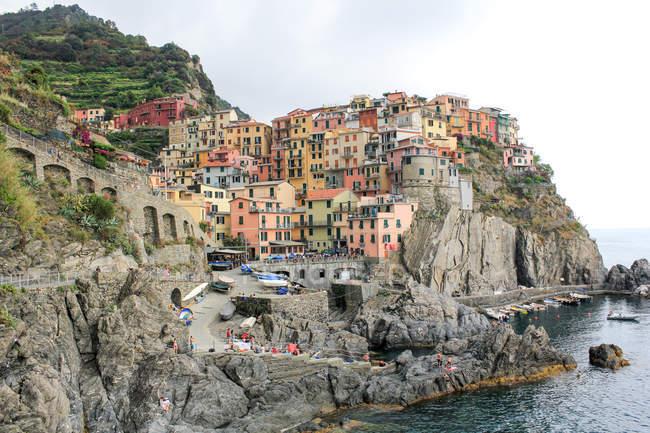 Casas coloridas ao longo da costa mediterrânea em Manarola, Ligúria, Itália — Fotografia de Stock