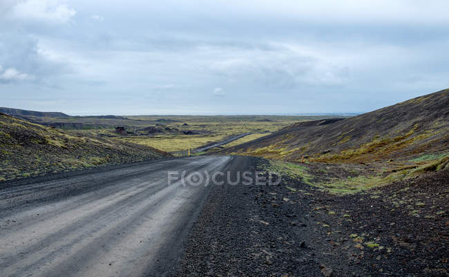 Dirt road with distant landscape under cloudy sky, Iceland — Stock Photo