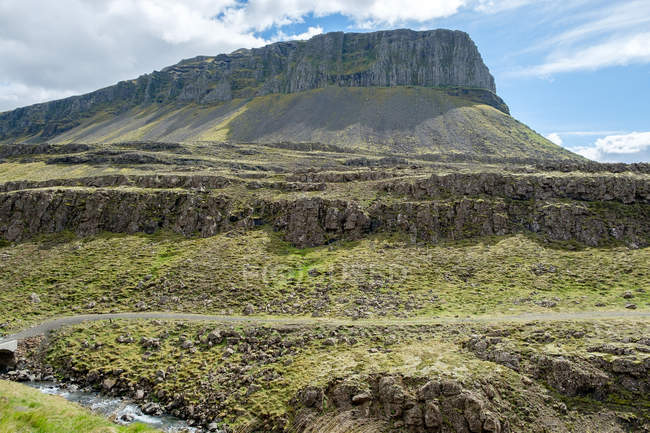 Mountainous landscape with winding road in sunlight, Iceland — Stock Photo