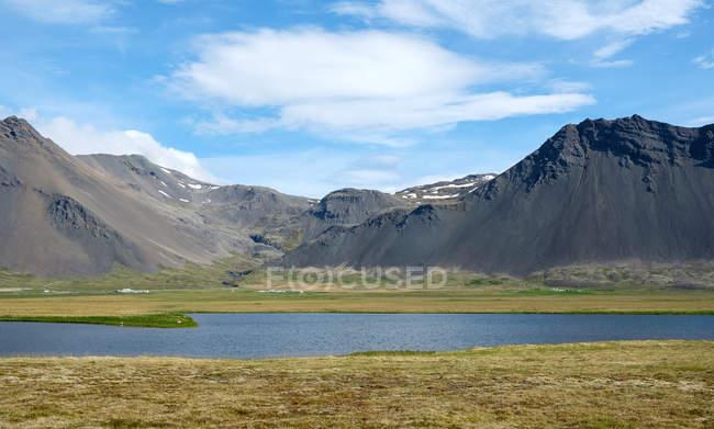 Paisagem sol iluminado com montanhas e lago, Islândia — Fotografia de Stock