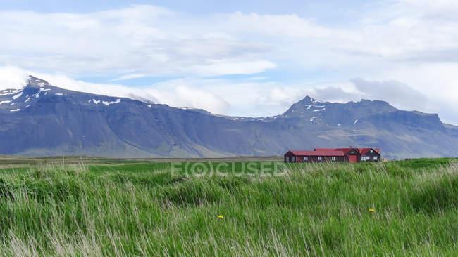 Fernen landwirtschaftliches Gebäude auf der grünen Wiese unter Bergen — Stockfoto