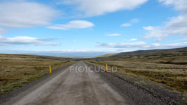 Dirt road with distant landscape under blue cloudy sky, Iceland — Stock Photo