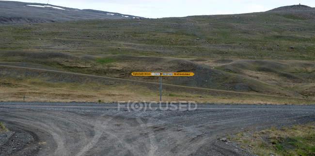 Richtung Zeichen auf Feldweg mit Hügeln im Hintergrund, Island — Stockfoto