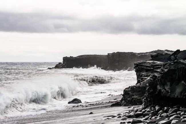 Marina de Estados Unidos, Hawai, con olas rompiendo en las rocas de lava por la playa de Kalapana - foto de stock