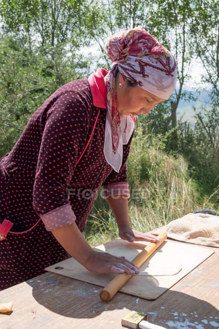 Femme cuisson pâte à la cuisine extérieure, Ak Say, Issyk-Kul région, Kirghizistan — Photo de stock