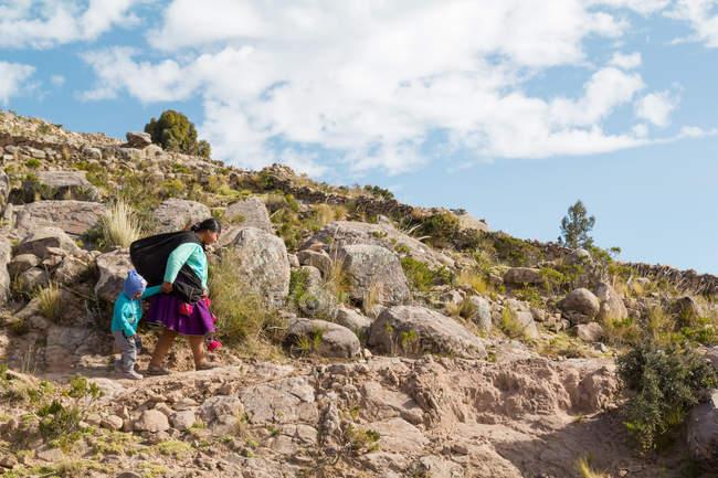 Mère et petite fille marche sur une route de campagne, Puno, Pérou — Photo de stock