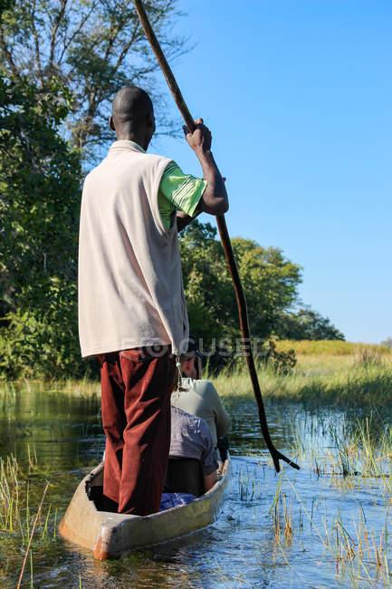 Botswana Okavango-Delta, afrikanische Steuerelemente Mokoro mit vier Meter langen GRUB-Boot — Stockfoto