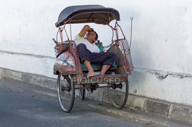 Sleeping rickshaw driver on city street, Jogyakarta, Java, Indonesia — стоковое фото