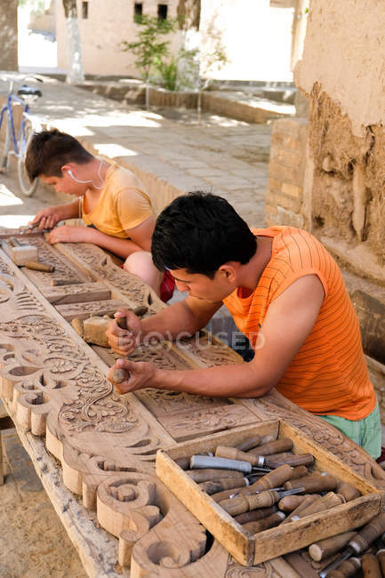 Local men carving gates and doors with ornate ornaments in Khiva, Uzbekistan. — Stock Photo