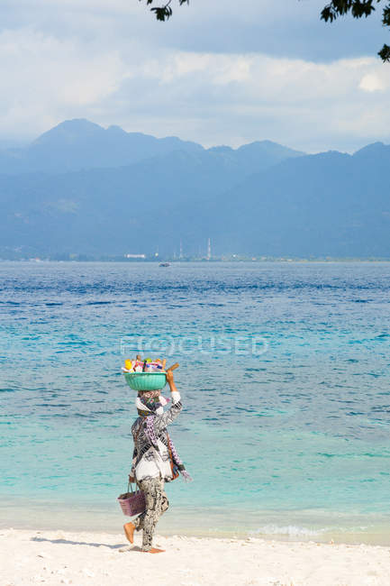 Indonesia, Nusa Tenggara Barat, Lombok Utara, woman carrying basket on head on beach — Stock Photo