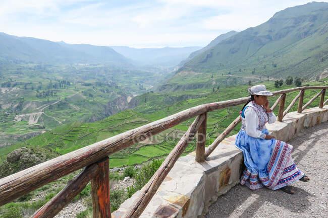 Woman sitting on fence at Colca Canyon, Caylloma, Arequipa, Peru — Photo de stock