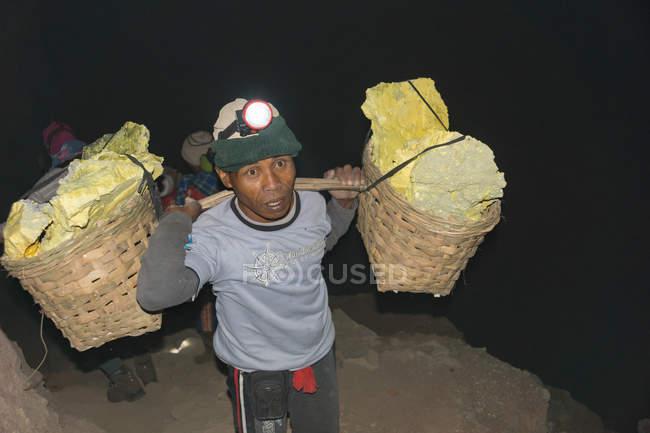 JAVA, INDONESIA - 18 DE JUNIO DE 2018: Minería de azufre en el volcán Ijen, hombre llevando canastas con azufre en la madrugada - foto de stock